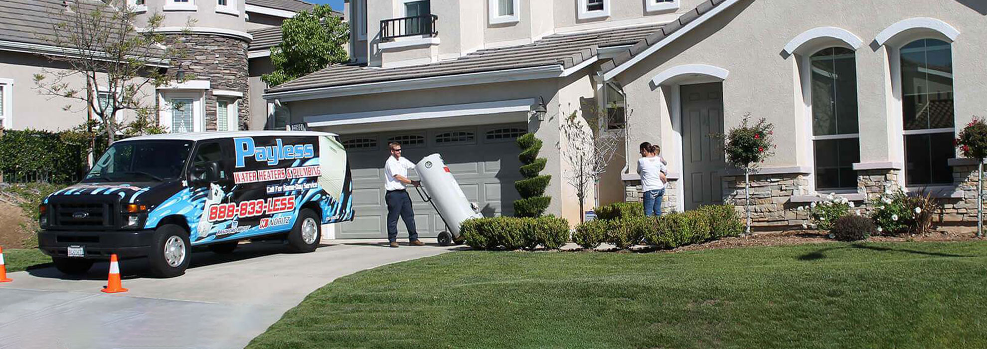 Payless truck in a driveway while technician walks water heater to the door.