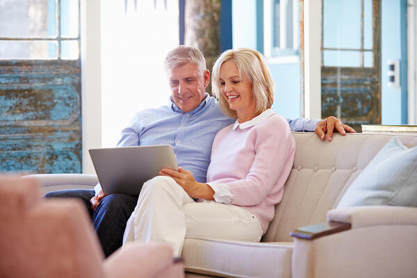 Couple sitting on couch looking at laptop.
